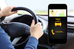 Phone with interface taxi on background man drivin Royalty Free Stock Photography