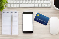Phone with isolated screen and credit card on the table Royalty Free Stock Photos