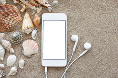 Phone with isolated screen and headphones on the sand. Phone with isolated screen and headphones lying on the sand with shells royalty free stock image