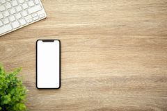 Phone with isolated screen on wooden table with a keyboard stock photo