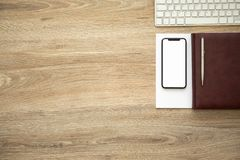 Phone with isolated screen on wooden table notebook and keyboard Stock Photos