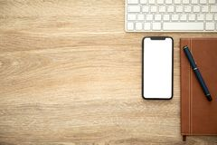 Phone with isolated screen on wooden table notebook and keyboard Royalty Free Stock Photos