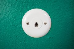 Phone Jack on Green Wall. Telephone jack in a green wall, with circular cover held in place by two screws Royalty Free Stock Photography