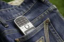 Phone and jeans. The phone is on the jeans in the field Stock Image