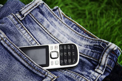 Phone and jeans. The phone is on the jeans in the field Royalty Free Stock Photos