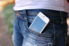 Phone in jeans pocket. White phone in jeans pocket Royalty Free Stock Images
