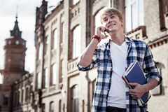 Joyful positive student sharing news. On the phone. Joyful positive young man holding his manuals and sharing his news while talking on the phone royalty free stock image
