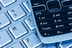 Phone on keyboard in blue tint Stock Photography
