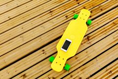 The phone lies on a yellow plastic longboard, which is located on the wooden flooring. Top view royalty free stock photography