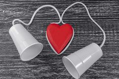 The phone is made of white plastic cups and a white rope laid around a red wooden heart royalty free stock photos