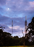 Phone masts in nature under a full moon at twiligh Royalty Free Stock Images