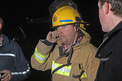 Phone message. Volunteer fire fighter relays messages on a mobile phone during an evening bushfire, Westland, New Zealand Stock Photo