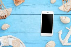 Phone mockup on blue wooden table surrounded with sea shells, anchor, boat life belt. Concept of use mobile phone on summer, beach travel royalty free stock photography