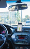 Phone and mounted holder in car on rural road. Gps royalty free stock photo
