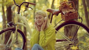 Phone music. Autumn woman in autumn park with green pullover. Headphones concept. Enjoy. Autumn Beauty. Blond beautiful. Woman listening to music on a meadow stock video