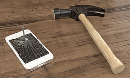 Phone nailed to table with hammer Royalty Free Stock Image