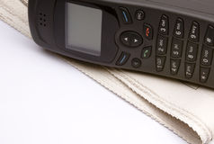 Phone with the newspaper. Black phone with the newspaper on a white background Royalty Free Stock Photos