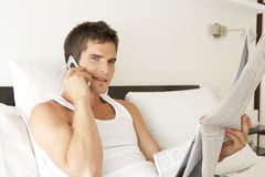 With Phone and Newspaper on Bed Stock Image