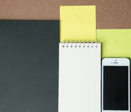 Phone and notebooks, post-it on the brown background. Phone and notebooks, post-it on the brown desk Stock Photo