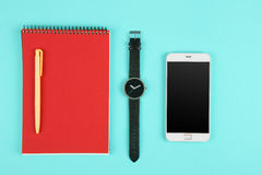 Phone, notepad, watch and pen on the color background Stock Image
