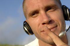 Phone operator. Face of young caucasian man with headphone Royalty Free Stock Images