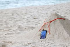 Phone and earphone on the sand on the beach Royalty Free Stock Image