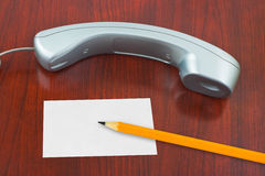 Phone, paper card and pencil Stock Images