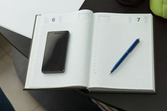 Phone and Pen on Clean Notebook. Modern Mobile Phone and Blue Pen on Clean Notebook on Black Table Royalty Free Stock Photo