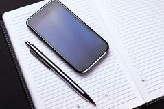 Phone, pen and notebook on black Stock Photos
