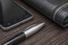 Phone with a pen and purse on a wooden background royalty free stock images