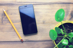 Phone, pencil and flower. Office wooden desk with smartphone and plant Stock Photos