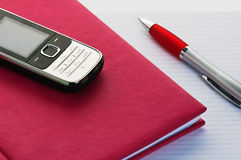 Phone and pencil with a notebook. Stock Images
