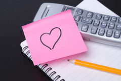 Phone and pink HEART postit. Phone, and pink postit with heart, on a spiral notebook. Business or lifestyle concept. Valentine's day Stock Photo