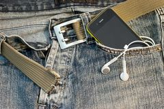 Phone in the pocket. A mobile phone in the pocket of denim trousers Stock Image
