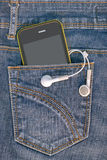 Phone in the pocket. A mobile phone in the pocket of denim trousers Stock Photos