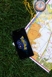 Phone with Pokemon Go application on screen, maps and compas. Stock Photography
