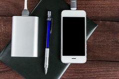 Phone and power bank connected by cord with pen and notebook on Royalty Free Stock Photography