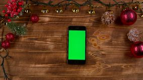 Phone is put on the table around the New Year`s lights are burning. Top view. Phone is put on a wooden table around the New Year`s lights are burning creating a stock video footage