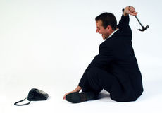 Phone Rage. Man smashing telephone with a hammer royalty free stock photos