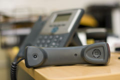 Phone Receiver. On a busy desk with the phone blurred in the back Royalty Free Stock Image