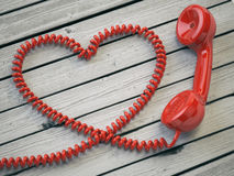 Phone reciever and cord as heart on white wooden background. Lov Stock Images