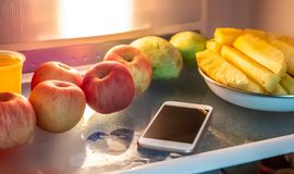 Phone in the refrigerator. stock photos