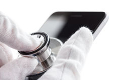 Phone repair and service concept. Smartphone diagnostics with a stethoscope. Isolated on white. Phone repair and service concept. Smartphone being diagnosed with stock photos
