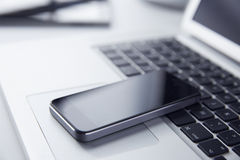 Phone resting on a Laptop Computer Stock Image