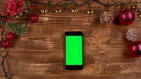Phone is on the table, next to the New Year`s lights. Top view. Phone rests on a wooden table, next to the New Year`s lights and different toys. Top view stock video footage