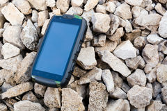 Phone on the rocks. Shockproof phone on the rocks Stock Images