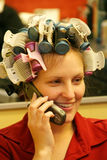 On the phone at the salon. Attractive young Caucasian blonde woman having hair styled for special event Stock Photos