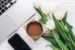 Phone screen and laptop with morning coffee and tulips on white royalty free stock photography