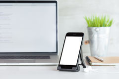 Phone showing white blank screen on work desk Royalty Free Stock Photos