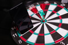 Phone stands on Darts field with Three Darts to hit red target close-up. Black mobile phone with blank screen stands on target close-up of Two red and one green royalty free stock image